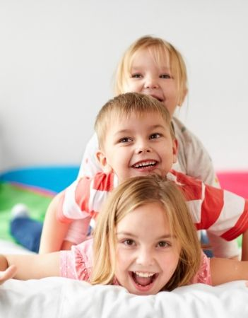 Image: three siblings laying on top of each other laughing