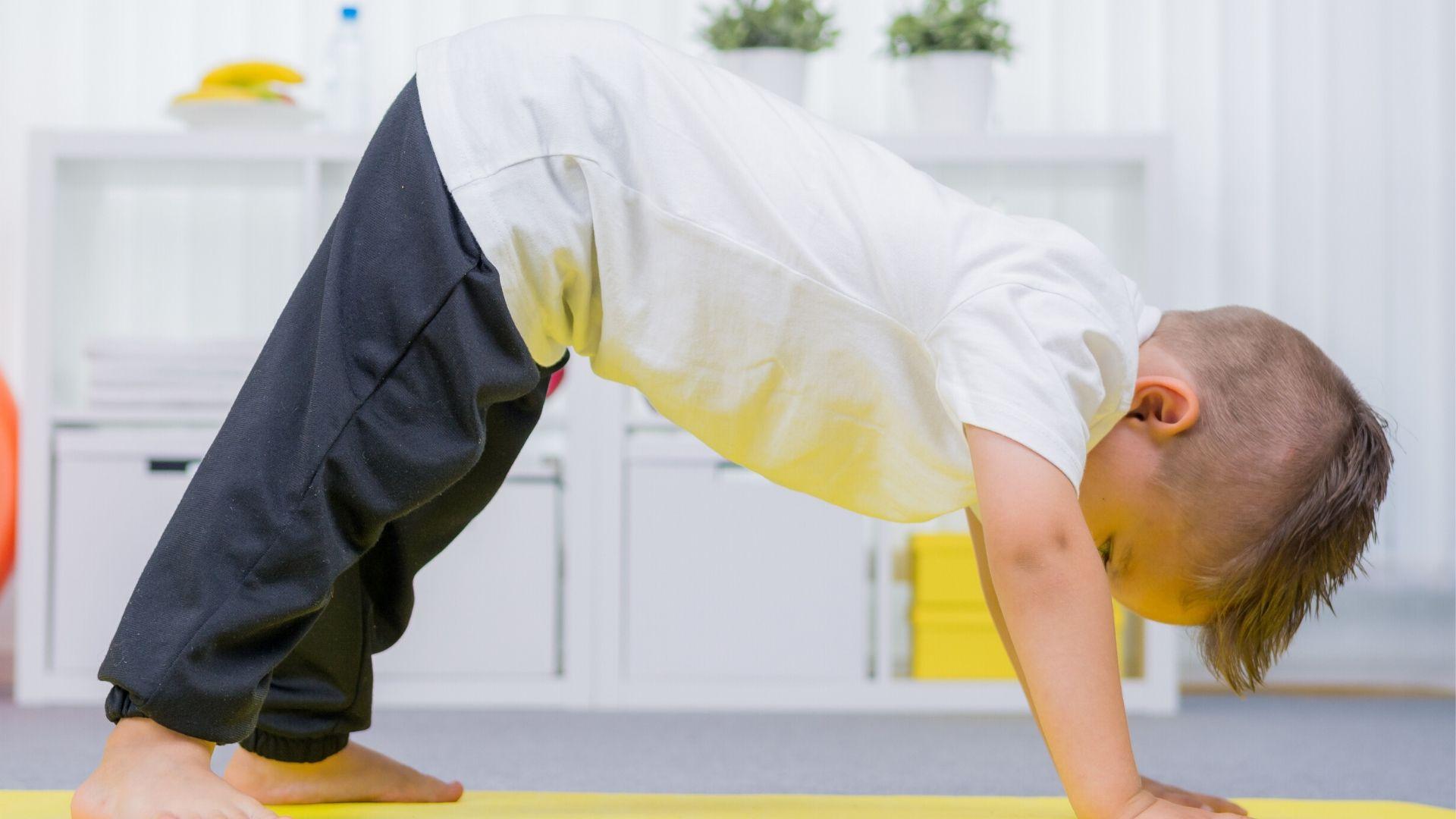 preschool boy on a yoga mat stretching